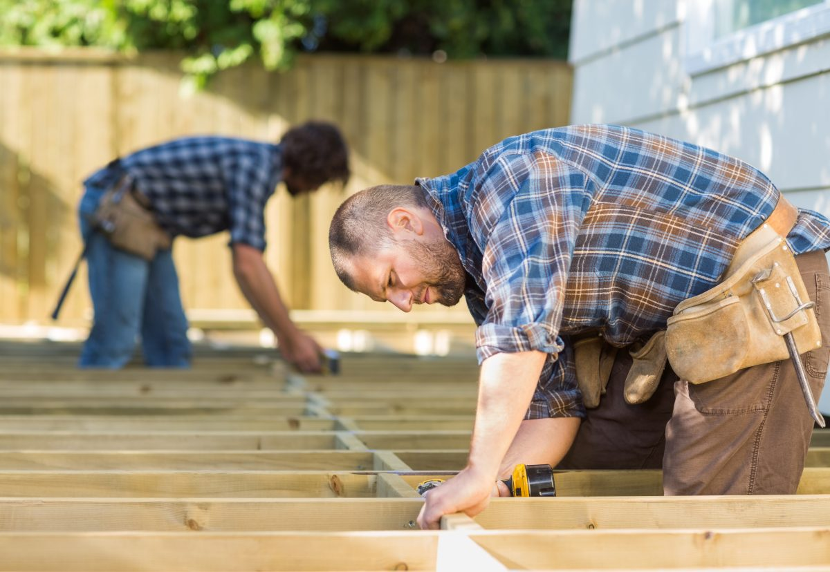 men work on a home improvement project new deck build